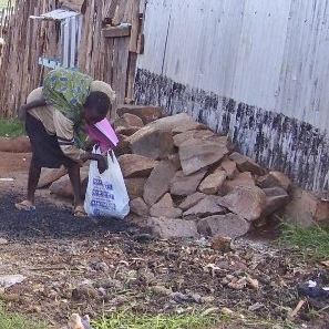 Ester carries her baby sister as she searches for food in the trash