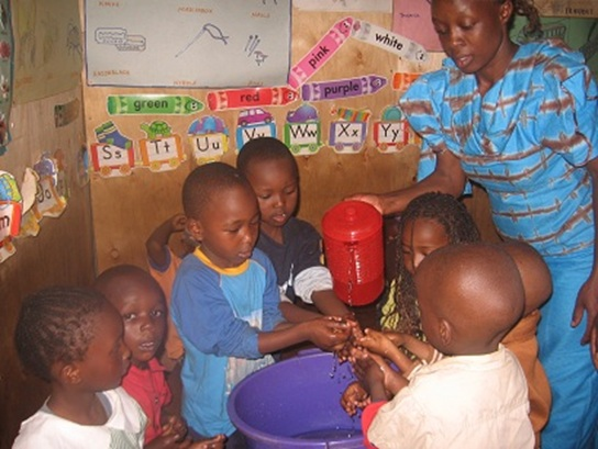 Teacher Karen uses the Kenyan approach to wash the hands of children before a meal