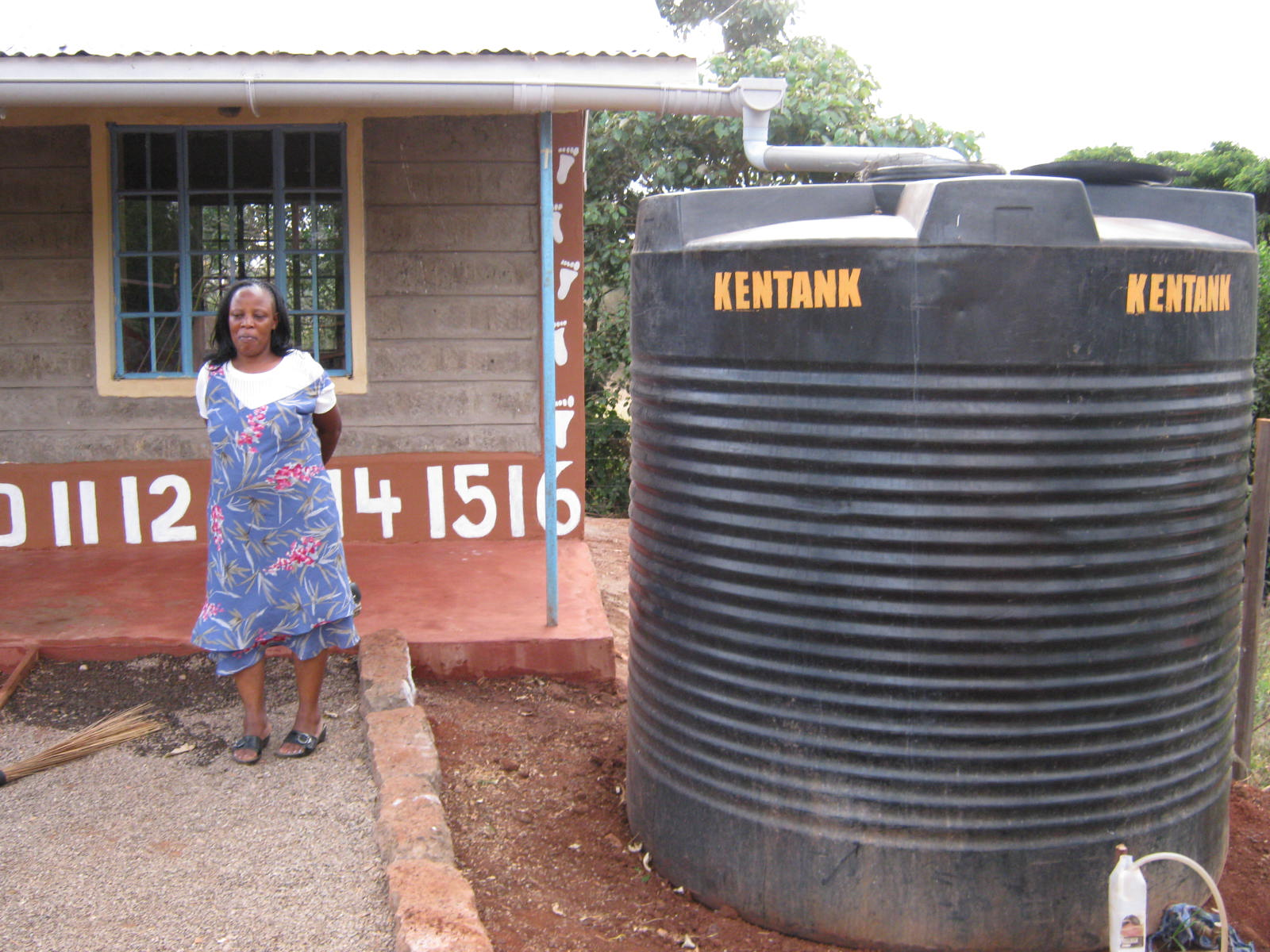 Mama Margaret stands by the school's 5000 liter water tank